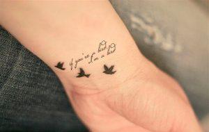 Tatuagens Femininas no braço frase com passaros