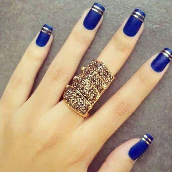 unha decorada azul com listras douradas nas pontas