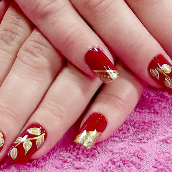 unha decorada vermelha com desenho dourado
